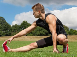 man-in-black-stretching-on-grass